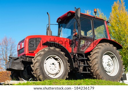 Modern red tractor on blue sky background. Outdoors