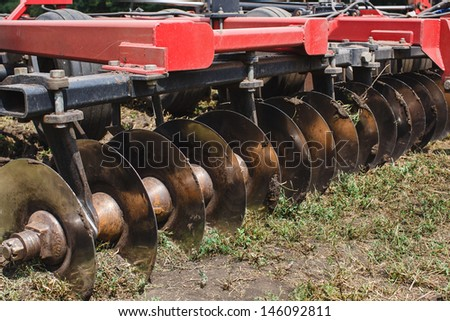 modern red tractor plows an agricultural field . The plow tractor plunges into arable land . - stock photo