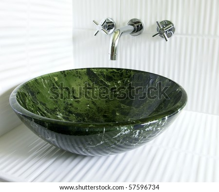Modern renovated bathroom with tempered glass green marble imitation vessel sink and superb old style wall mount faucet on crisp white corrugated ceramic tiles. - stock photo