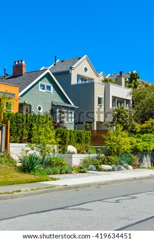 Modern residential houses on the street with landscaped front yards on terraces - stock photo
