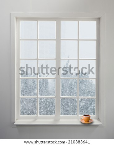 Modern residential window with a cup of tea and snowstorm on the background - stock photo
