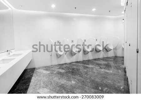 modern restroom interior with urinal row - stock photo