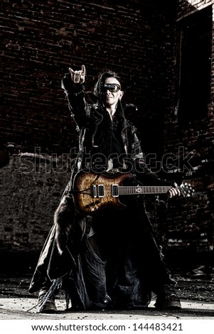 Modern rock musician playing the guitar outdoor. - stock photo