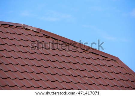 Modern roof covered with tile effect PVC coated brown metal roof sheets against a blue sky