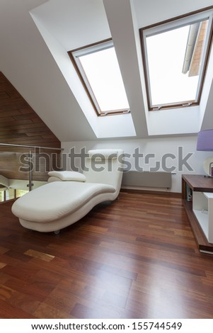 Modern room on the attic with comfortable seat - stock photo