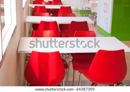 Modern room with red chairs and white table. - stock photo