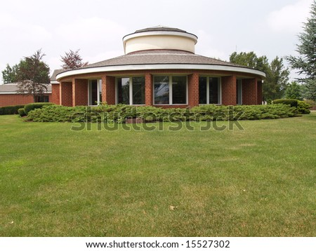 modern round brick building with many windows and green lawn - stock photo