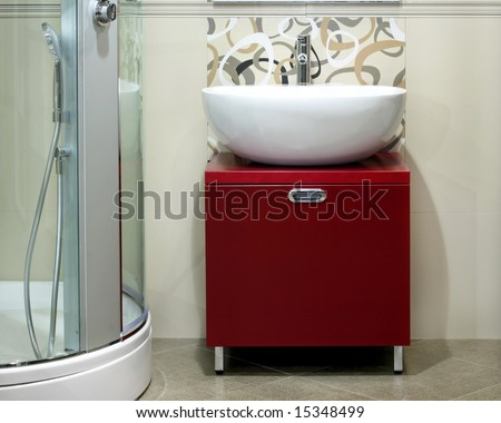 Modern round white basin over red cabinet - stock photo