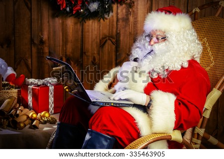 Modern Santa Claus at his wooden house working on his laptop and smoking a pipe. Christmas. - stock photo