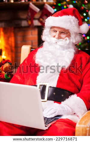 Modern Santa Claus. Cheerful Santa Claus working on laptop and smiling while sitting at his chair with fireplace and Christmas Tree in the background  - stock photo