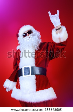 Modern Santa Claus in sunglasses over Christmas red background.  - stock photo
