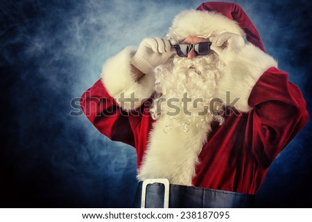 Modern Santa Claus in sunglasses over dark background. Christmas.  - stock photo