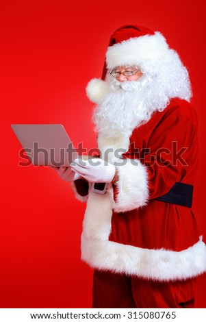 Modern Santa Claus using laptop computer over red background. Christmas. - stock photo