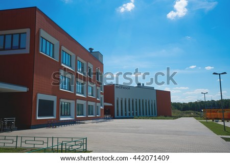 Modern school building. Empty school yard. Sunny day, blue sky. - stock photo
