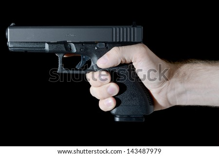 Modern semi-automatic pistol held in profile by caucasian hand. - stock photo