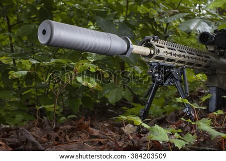 Modern semi automatic rifle that has a suppressor on the barrel - stock photo