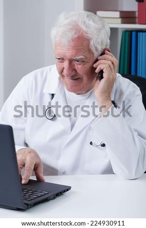 Modern senior doctor using phone and laptop - stock photo