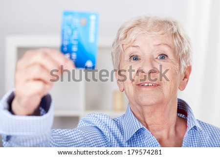 Modern senior lady with credit card, horizontal - stock photo