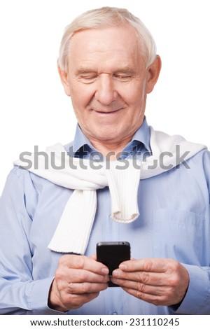Modern senior man . Happy senior man holding mobile phone while standing against white  - stock photo