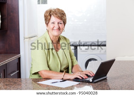 modern senior woman using laptop computer at home - stock photo