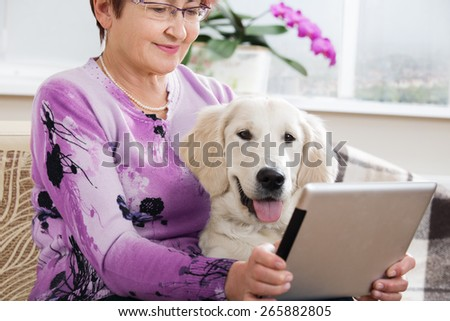 Modern senior woman with her pet looking at digital tablet - stock photo