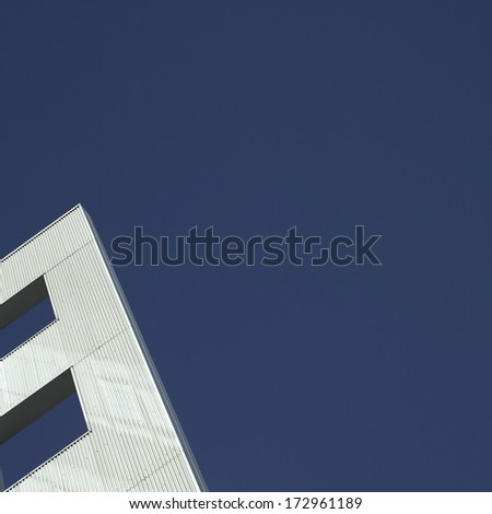 Modern silver building with clear blue sky - stock photo