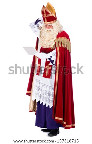 Modern Sinterklaas using a tablet instead of his book - stock photo