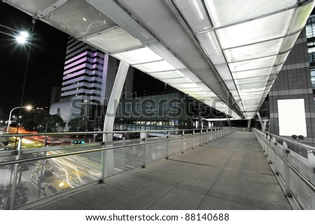modern skybridge with a big sing board on the right side and car trails on the left - stock photo