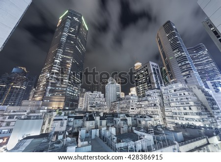 modern skyscraper and old residential building in Hong Kong city at night - stock photo