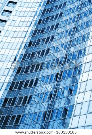 Modern skyscraper blue windows  glass wall with reflections - stock photo