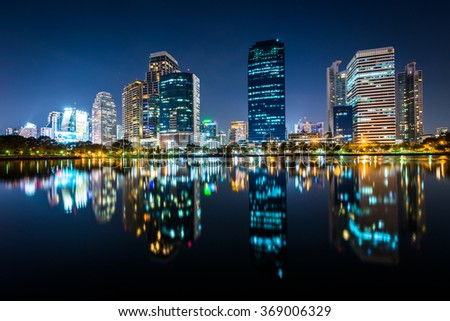Modern skyscrapers and Lake Rajada at night, at Benjakiti Park, in Bangkok, Thailand.