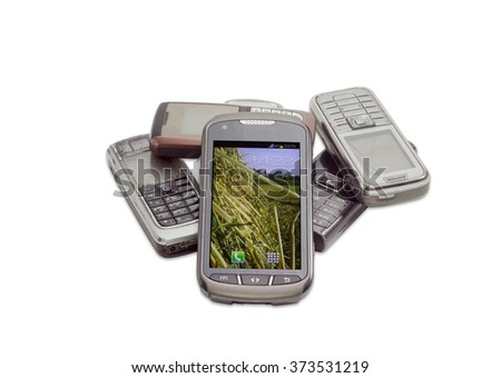 Modern smart-phone with touchscreen on the background of several old shabby outdated mobile phones on a light background  - stock photo