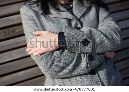 Modern smart wrist watch on hand of young girl in grey autumn coat. This person is always connected to social media and internet. Focus on watches,fingers.Unrecognizable white female model