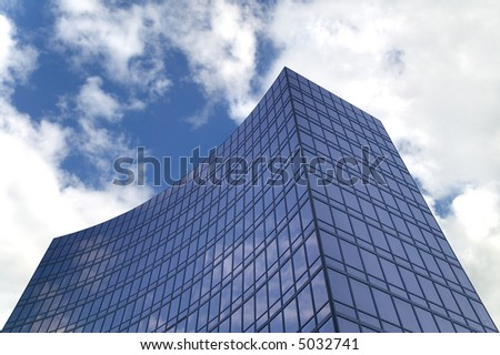 Modern smoked glass office building against a blue cloudy sky.