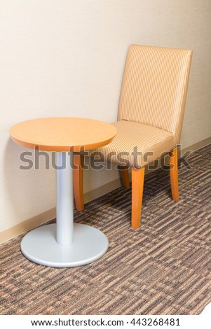 modern sofa chair and table in hotel room for a single person, feeling alone. - stock photo
