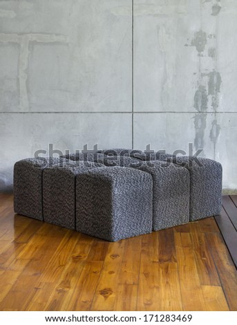 Modern sofa in empty room with concrete wall - stock photo