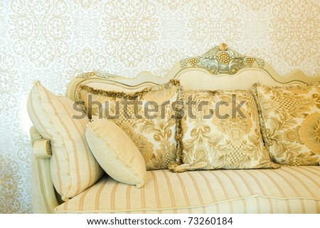Modern sofa with three cushions in front of beautiful wallpaper. - stock photo