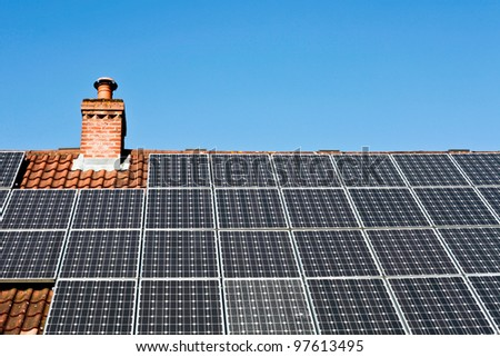 Modern solar panels on a tiled roof in the sunlight