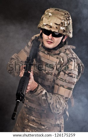 Modern soldier with rifle isolated on a black background