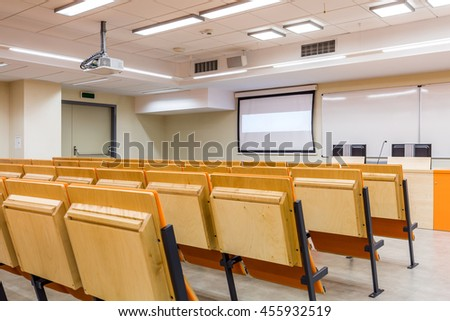 Modern space of lecture room with row of chairs, screen and whiteboards