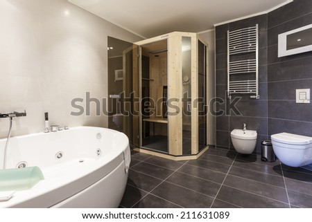 Modern spacious bathroom interior with jacuzzi bath and small sauna - stock photo