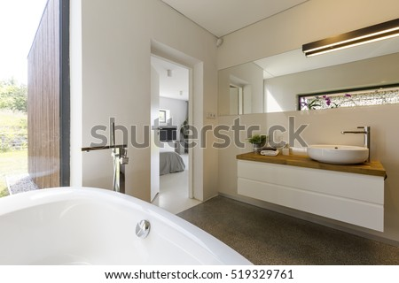 Modern spacious bathroom with white bathtube with garden view throught panoramic window