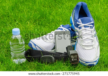 Modern sport equipment for running on the grass. Sneakers, water, smartphone, sport watch and heart sensor