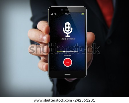 modern spy concept: businessman holding a sound recorder smartphone - stock photo