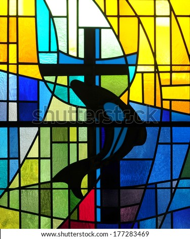 Modern stained glass window depicting Christian cross with dolphin, a symbol of friendship - stock photo