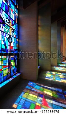Modern stained glass windows reflecting colors onto church walls and floor - stock photo