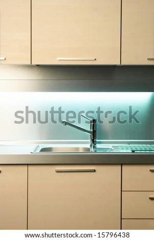 Modern stainless steel tap in white kitchen - stock photo