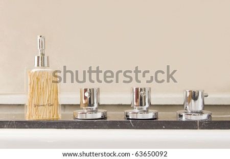 Modern stainless steel taps with shower gel - stock photo