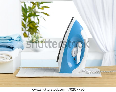 Modern steam iron on the the table in laundry room - stock photo