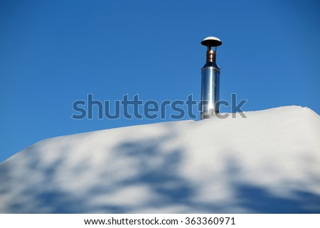 Modern steel chimney of a Russian sauna covered with snow against a blue sky - stock photo